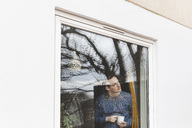 Man holding coffee cup looking through window while standing in house - MASF03016