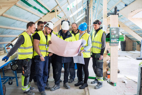Manager standing with manual workers while reading blue prints at construction site - MASF03022
