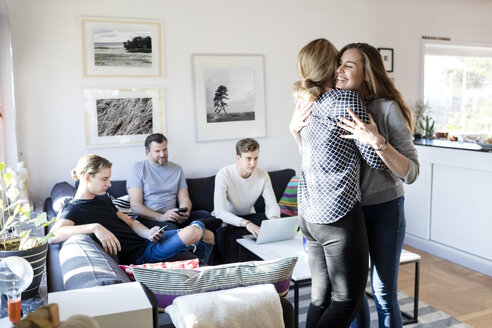 Mother and daughter embracing while family sitting on sofa in living room - MASF03025