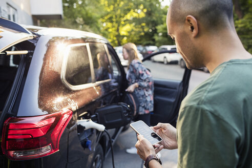 Man using smartphone with woman standing by car in background - MASF03037