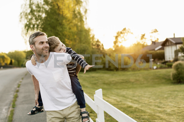 Happy father piggybacking son while standing by grassy field during sunset - MASF03049