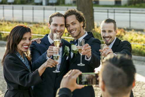 Happy friends with champagne flutes posing for photograph during wedding ceremony - MASF03061