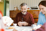 Happy senior man playing cards with family at home - MASF03076
