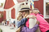 Happy friends embracing in back yard - MASF03085
