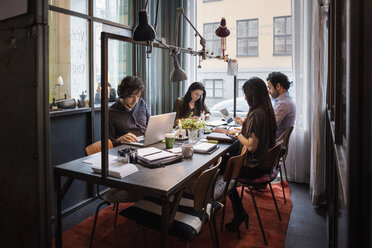 Male and female bloggers working at table in modern office - MASF03091