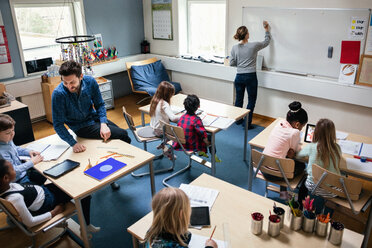 High angle view of female teacher writing on board while male educator sitting with students at desk in classroom - MASF03097