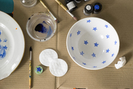 Overhead view of watercolor paints and brushes with bowls on cardboard - CAVF36473