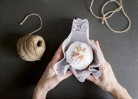 Cropped hands of woman wrapping cupcake on kitchen counter - CAVF36482
