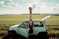 Playful boy standing on car roof with brother in vehicle at field against cloudy sky - CAVF36485
