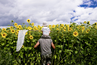 Rear view of son holding butterfly net while sitting on father's shoulder at sunflower field against cloudy sky - CAVF36491