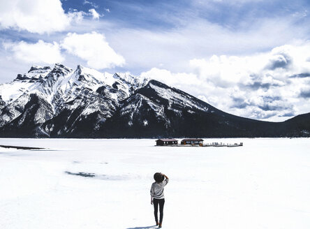 Rear view of woman looking at view while standing by frozen Lake Minnewanka against cloudy sky - CAVF36512