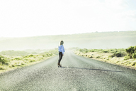 Rear view of woman skateboarding on country road against clear sky during sunny day - CAVF36521