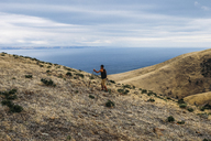 Hiker climbing mountain against sea and cloudy sky - CAVF36533