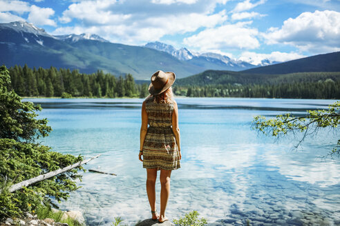 Rear view of woman in hat looking at view while standing on rock by lake at Jasper National Park - CAVF36542