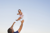 Low angle view of father throwing daughter into air against clear sky - CAVF36569