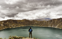 Rear view of man standing on cliff against Quilotoa and cloudy sky - CAVF36599