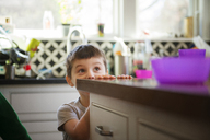 Boy hiding and playing in kitchen at home - CAVF36620