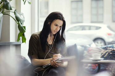 Creative businesswoman wearing headphones while writing in spiral notebook at office - MASF03119