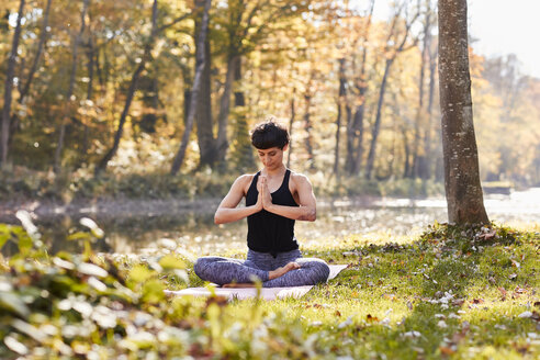 Mid adult woman in forest practicing yoga, meditation - SHOF00007