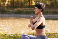 Mid adult woman at riverside practicing yoga, meditation - SHOF00010