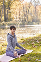 Smiling mid adult woman in forest practicing yoga, lotus position - SHOF00016