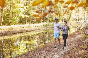 Couple jogging on autumnally forest track - SHOF00019