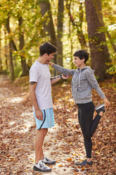 Couple stretching in autumn forest - SHOF00022