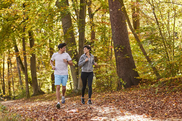 Couple jogging on autumnally forest track - SHOF00025