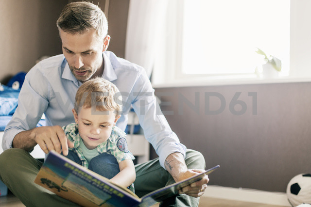 Father pointing and reading book to son while sitting on floor at home - MASF03174