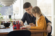 Father assisting daughter in homework at home - MASF03177