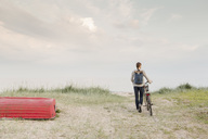 Full length of woman carrying backpack walking with bicycle at beach against sky - MASF03186
