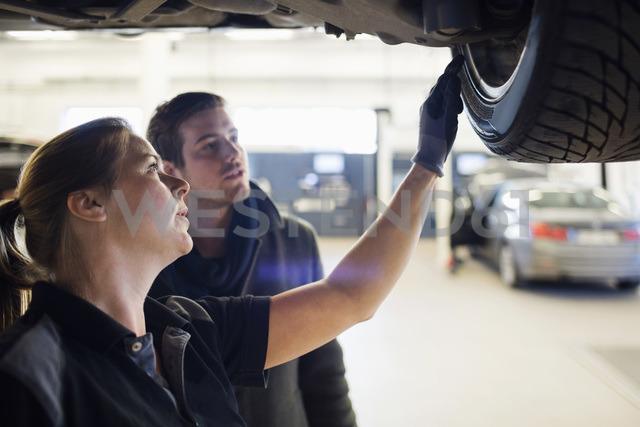 Close-up of mechanic showing wheel to customer under car at repair shop - MASF03204