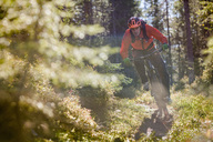 Biker riding mountain bike amidst trees on field in forest - MASF03207