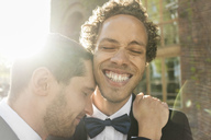 Close-up of gay man embracing cheerful newlywed partner with eyes closed - MASF03216