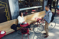 Businessman with bicycle talking to female colleague sitting at sidewalk cafe - MASF03222