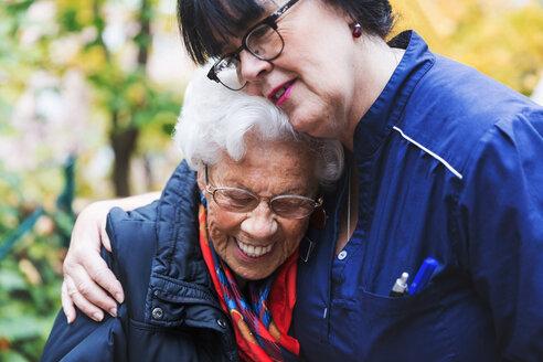 Caretaker embracing senior woman in park - MASF03225