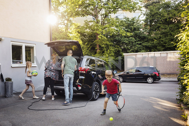 Children playing with balls while parents loading car trunk in back yard - MASF03243 - Maskot ./Westend61