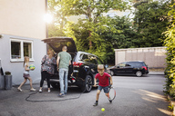 Children playing with balls while parents loading car trunk in back yard - MASF03243