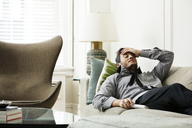 Tired businessman relaxing on sofa at home - CAVF36815