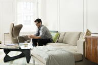 Businessman text messaging through smart phone while sitting on sofa - CAVF36818