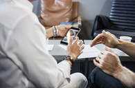 Cropped image of business people using mobile phone in office - CAVF36827