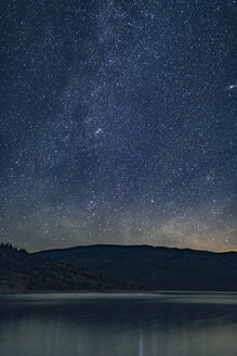 Sea by mountains against star field at night - CAVF36950
