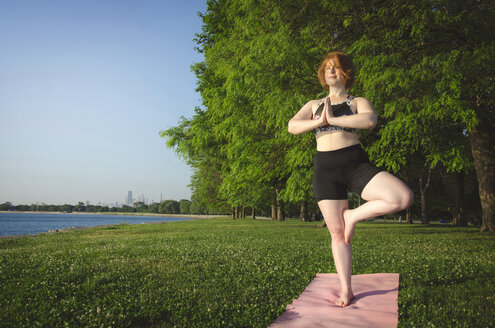Woman practicing tree pose yoga at park by sea against trees and clear sky - CAVF36983