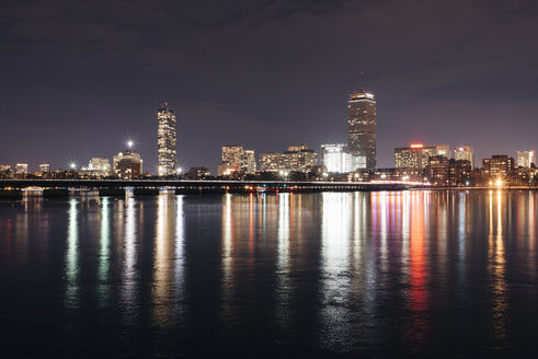 Charles river against illuminated cityscape at night - CAVF36989
