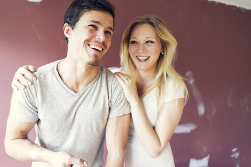 Happy couple standing against wall at home - CAVF37022