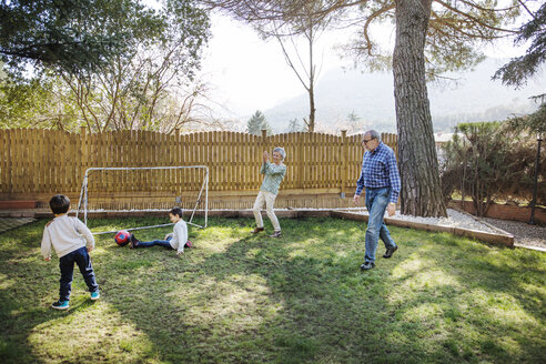 Cheerful grandparents playing soccer with grandsons at yard - CAVF37142