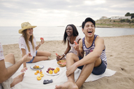 Cheerful friends eating fruits while sitting on beach - CAVF37199
