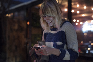 Happy woman using smart phone in illuminated city at night - CAVF37262
