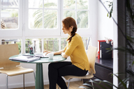 Businesswoman sitting on chair while working on laptop in creative office - CAVF37403