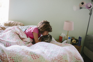 Girl kissing cat on bed at home - CAVF37595